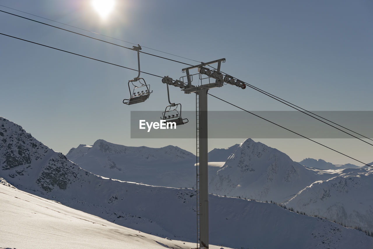 Low angle view of overhead cable car over snow covered mountain against sky