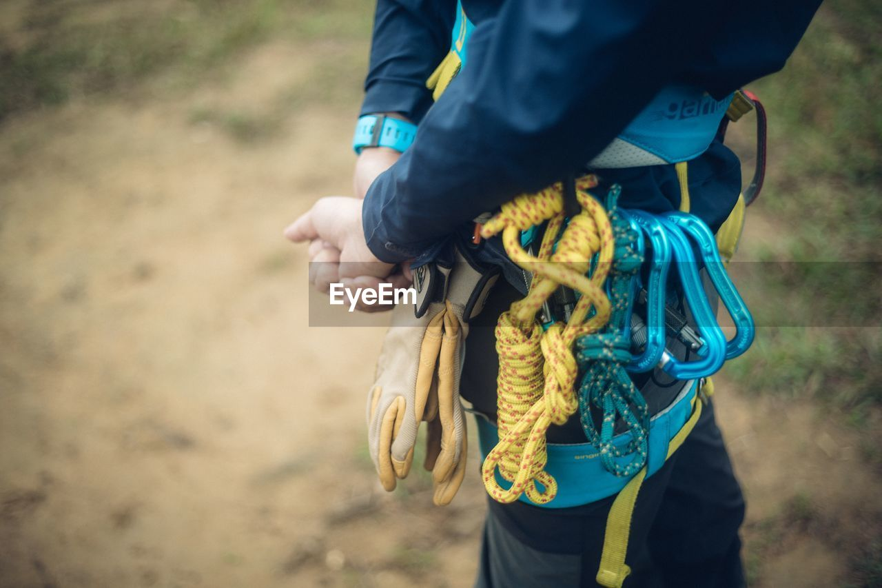 focus on foreground, real people, one person, day, midsection, holding, standing, human body part, hand, human hand, rope, land, outdoors, leisure activity, casual clothing, adult, tied knot, men, lifestyles, human limb