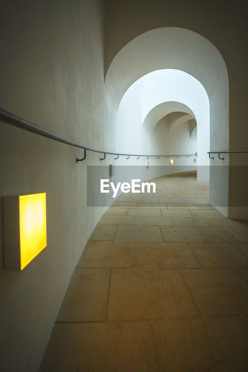 architecture, built structure, arch, illuminated, the way forward, lighting equipment, building, indoors, direction, arcade, no people, empty, wall - building feature, corridor, absence, wall, diminishing perspective, ceiling, light, electric lamp
