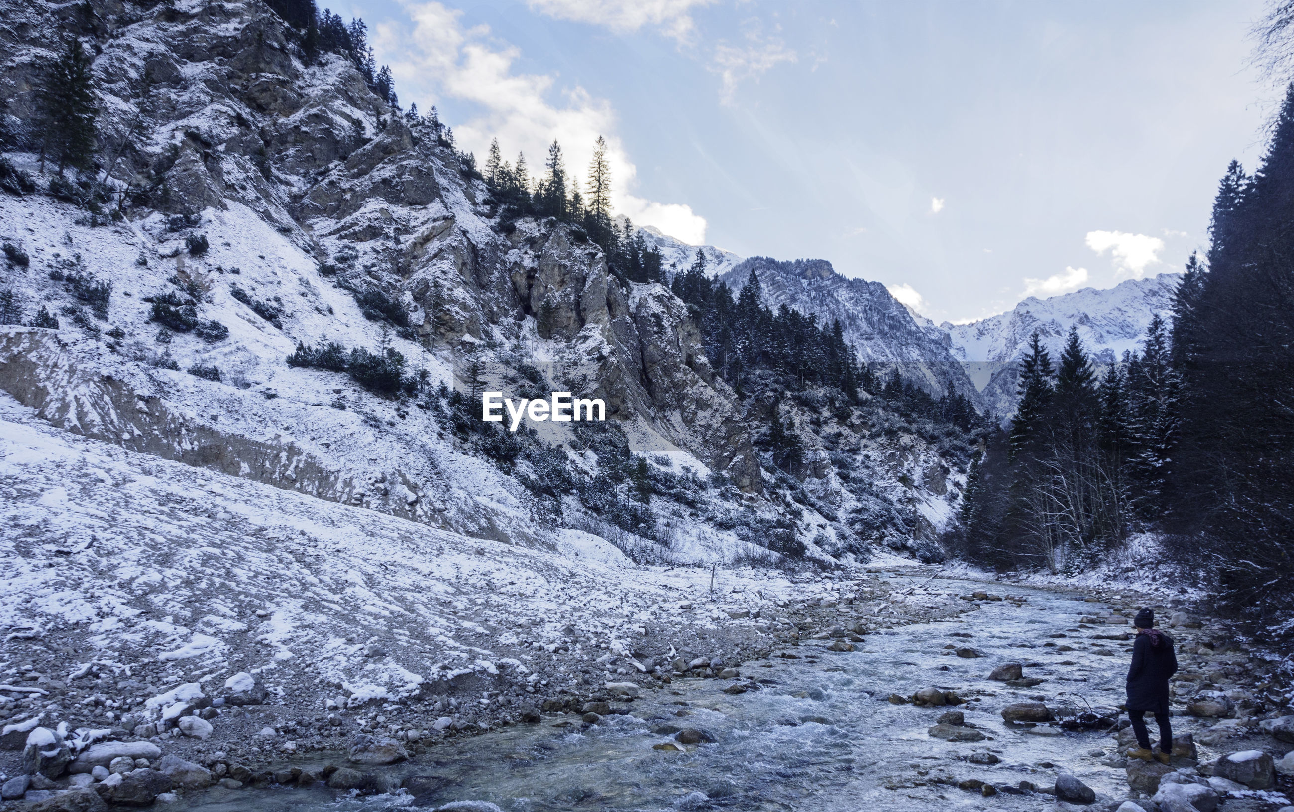 Full length of person standing by river against snow covered mountains