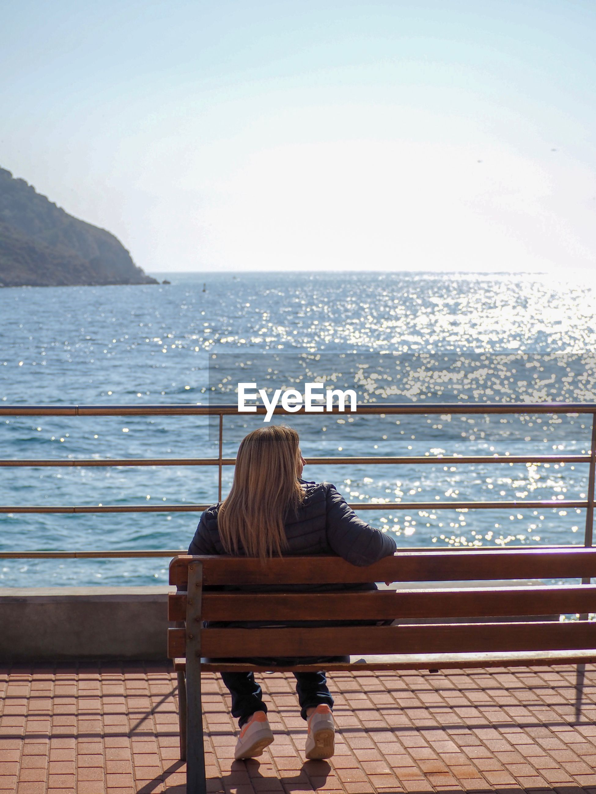 Rear view of woman sitting on bench while looking at sea