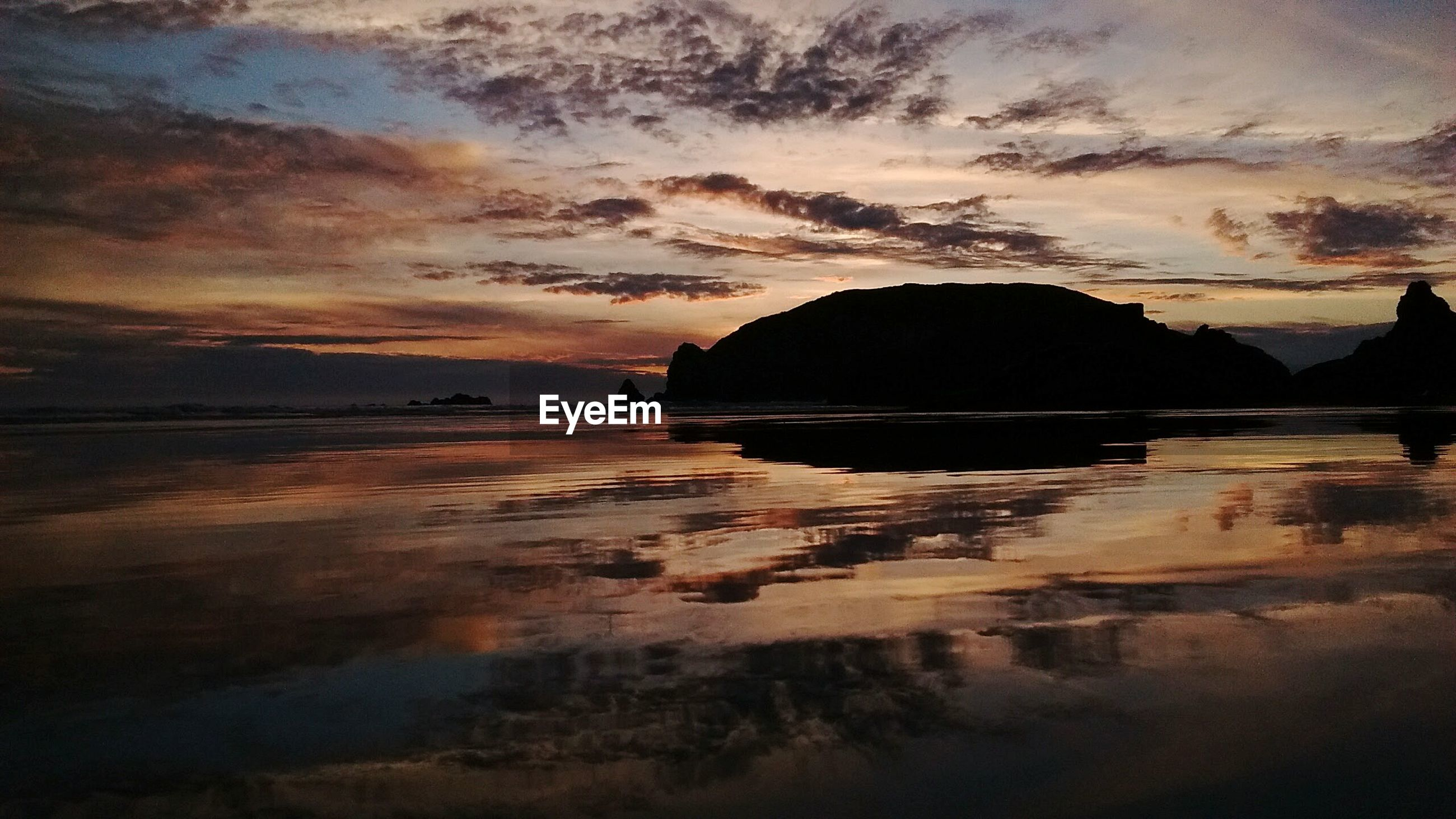 water, sunset, tranquil scene, silhouette, tranquility, scenics, sky, beauty in nature, sea, reflection, beach, nature, mountain, idyllic, dusk, shore, cloud - sky, sand, calm, outdoors