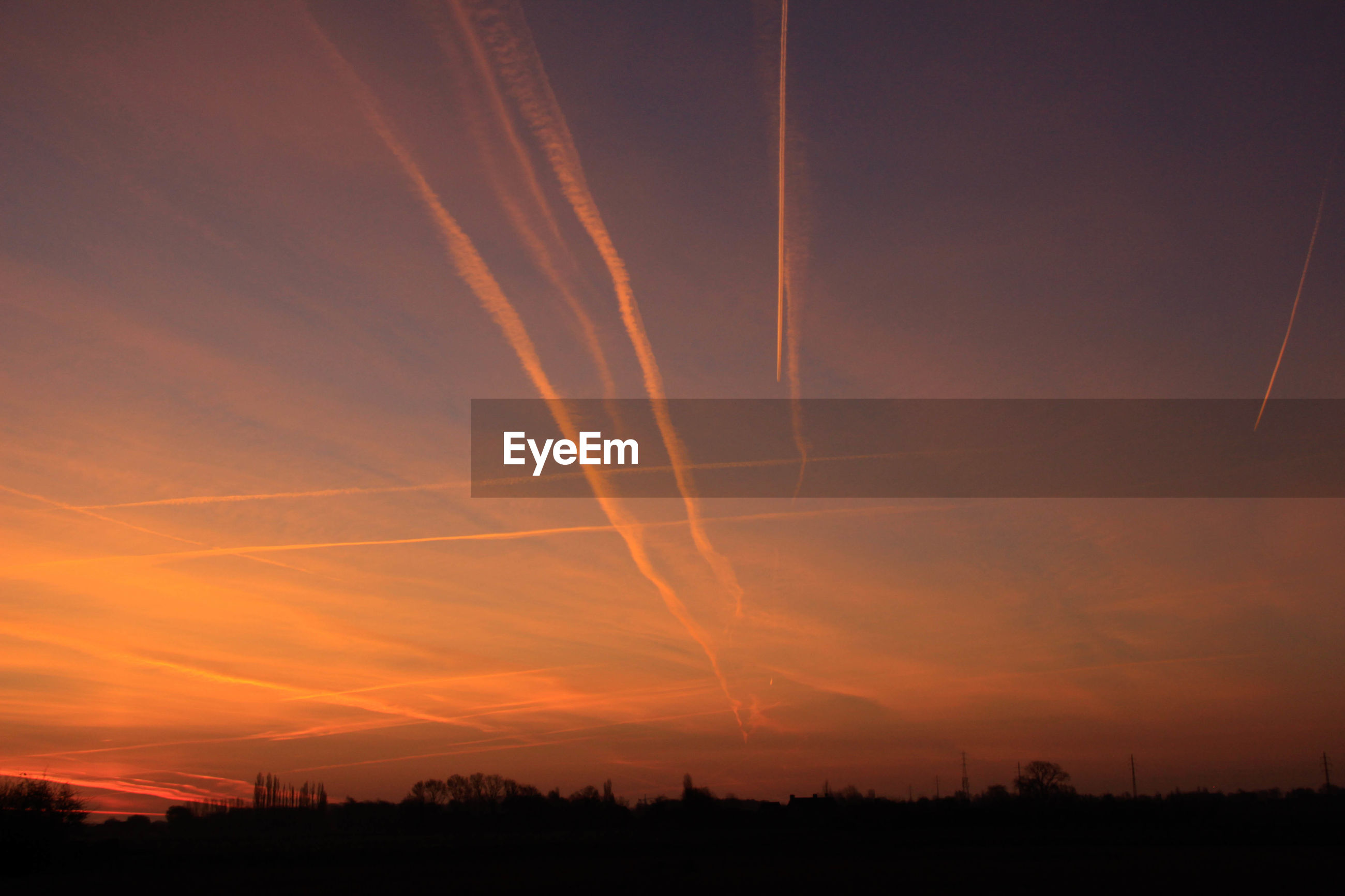 LOW ANGLE VIEW OF SILHOUETTE VAPOR TRAILS IN SKY