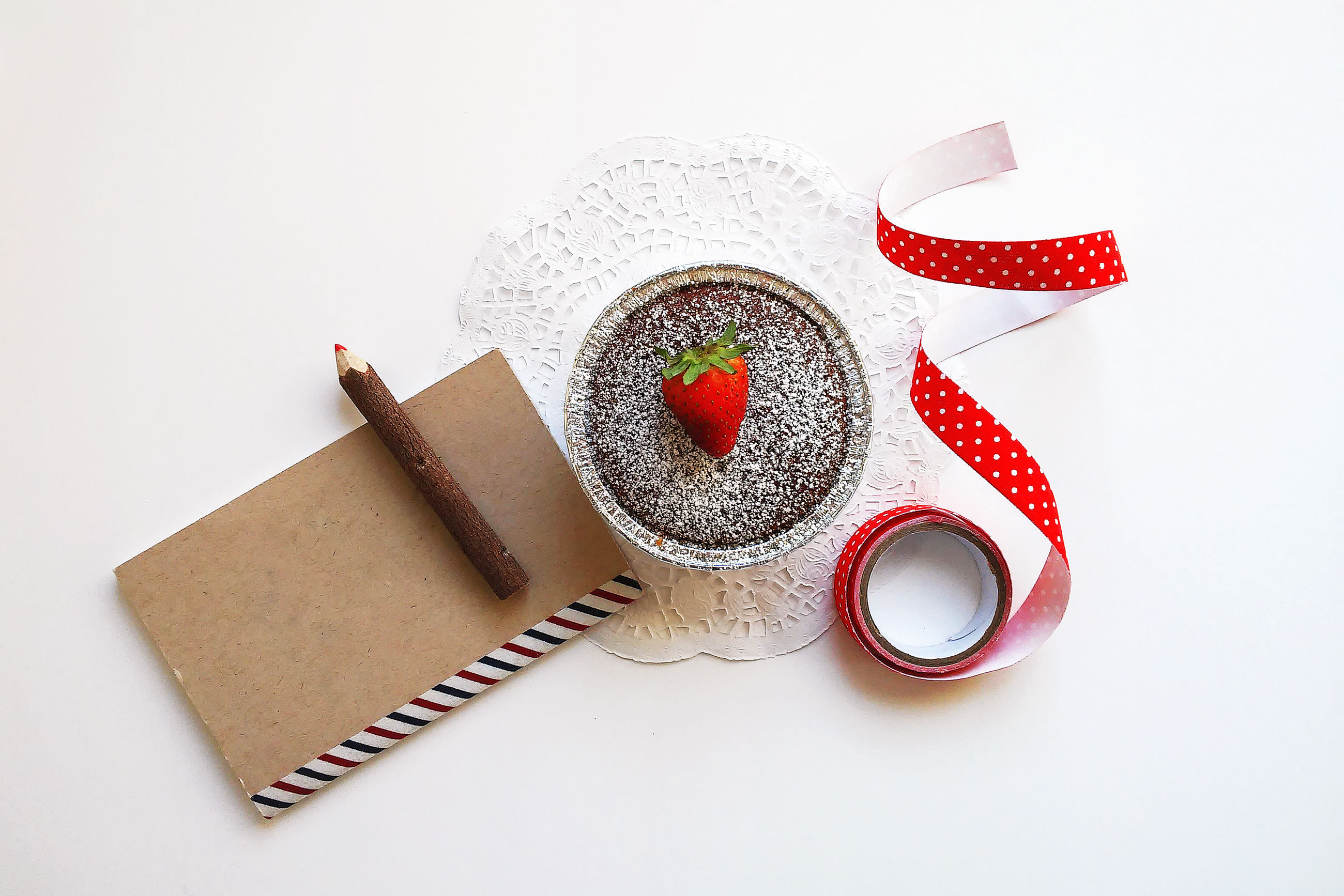 Directly above shot of dessert with book and ribbon on white background