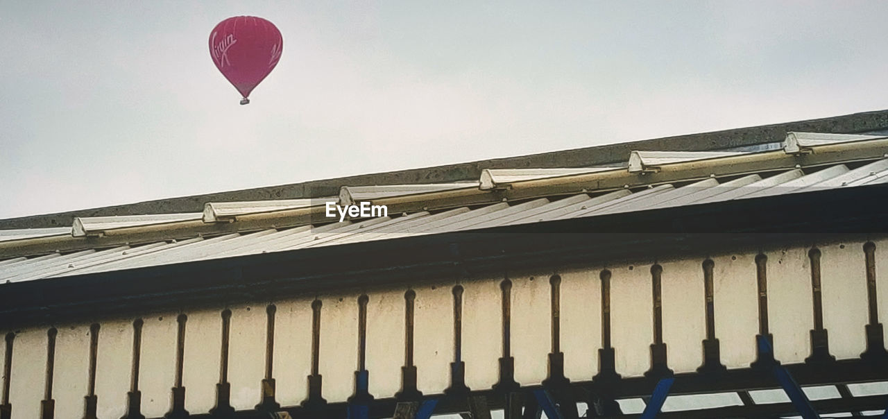 built structure, architecture, building exterior, low angle view, sky, roof, balloon, no people, day, building, nature, clear sky, transportation, outdoors, pattern, in a row, flying, city, mid-air, side by side