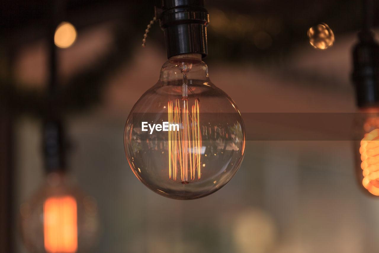 Close-Up Of Lit Light Bulb Against Blurred Background