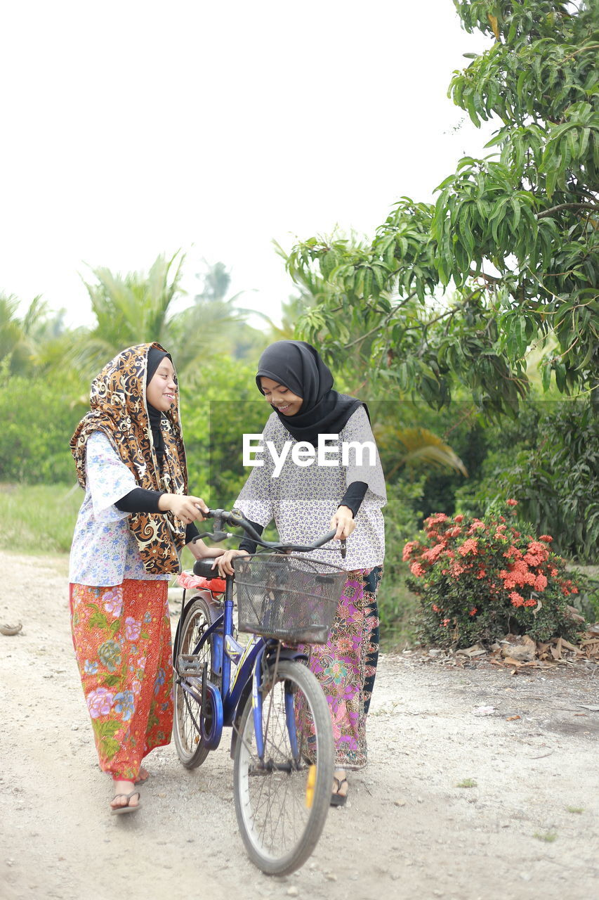 Sisters with bicycle on dirt road