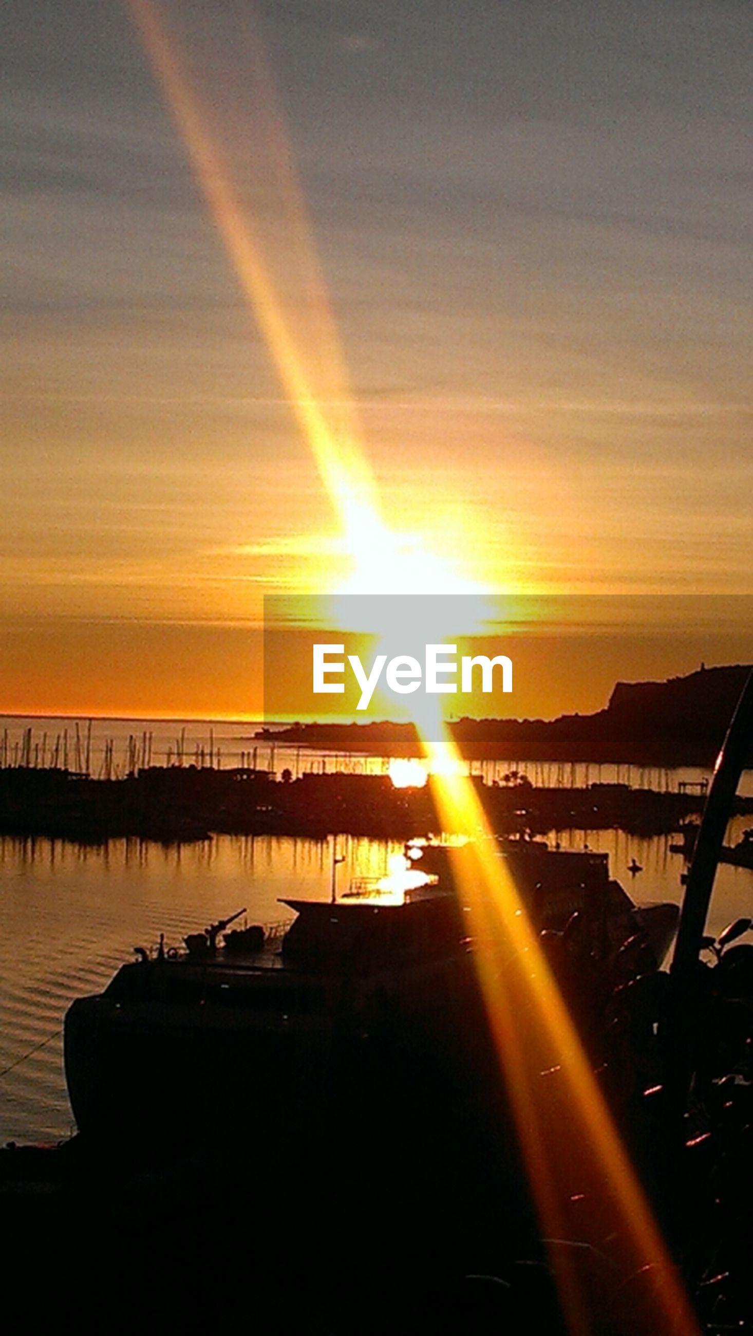 sunset, sun, orange color, sky, transportation, water, sunbeam, scenics, reflection, sunlight, beauty in nature, lens flare, silhouette, mode of transport, cloud - sky, nature, tranquil scene, sea, tranquility, idyllic