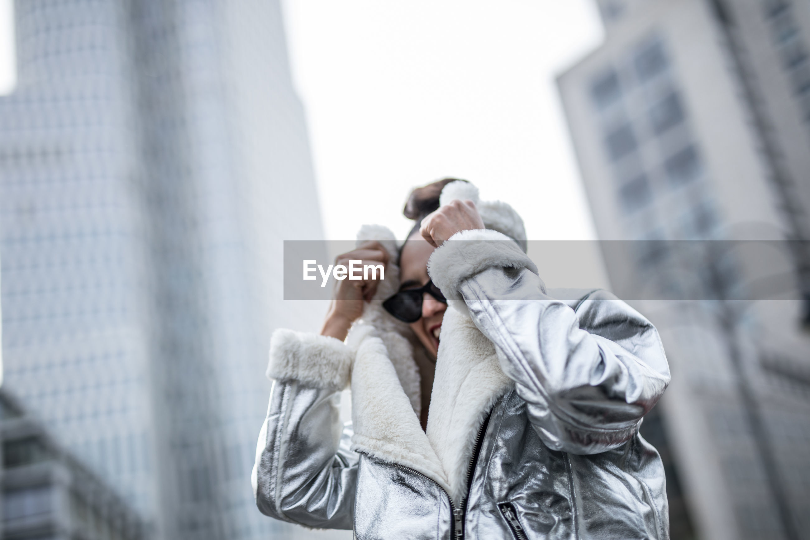 Low angle view of cheerful woman wearing warm clothing in city