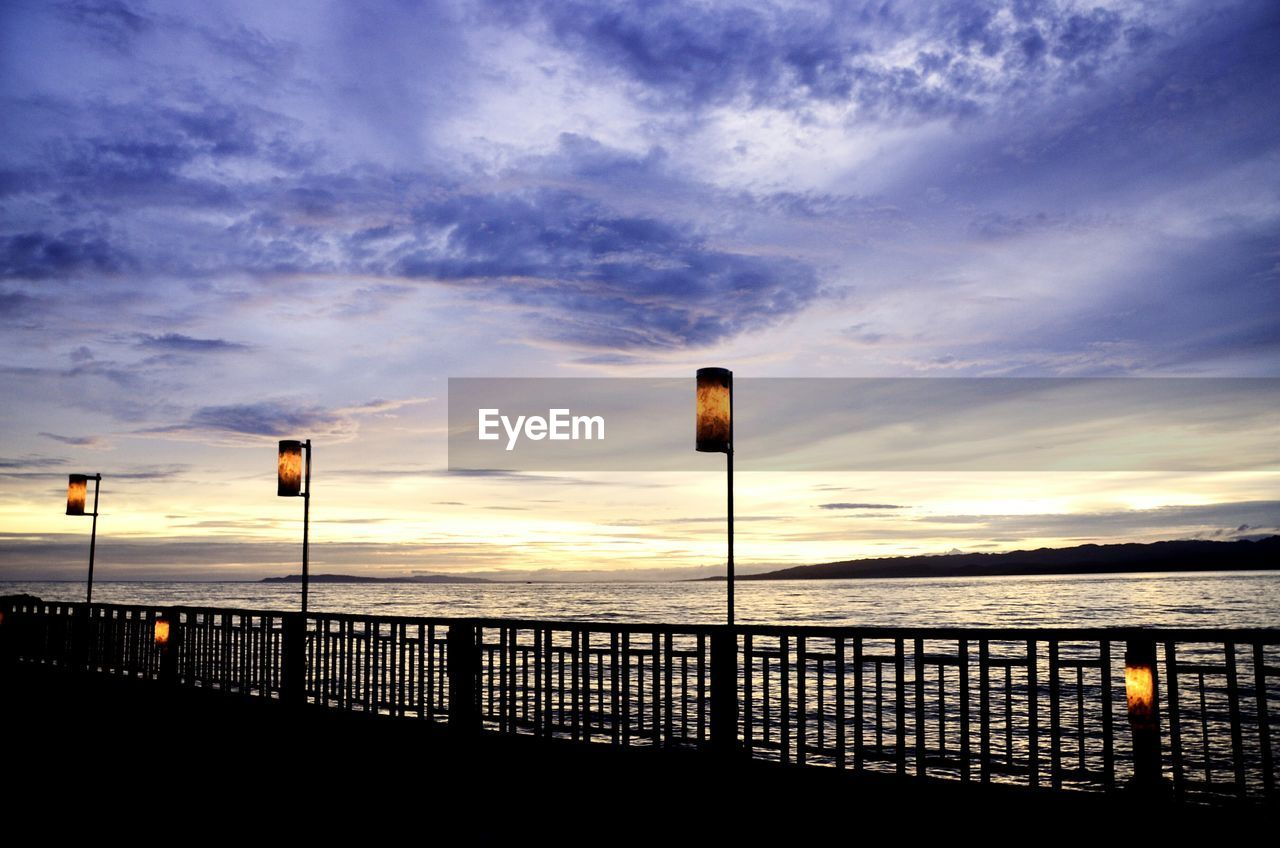 sky, cloud - sky, sunset, water, sea, railing, scenics - nature, beauty in nature, street light, nature, street, no people, tranquility, tranquil scene, lighting equipment, silhouette, outdoors, built structure, idyllic, horizon over water, light