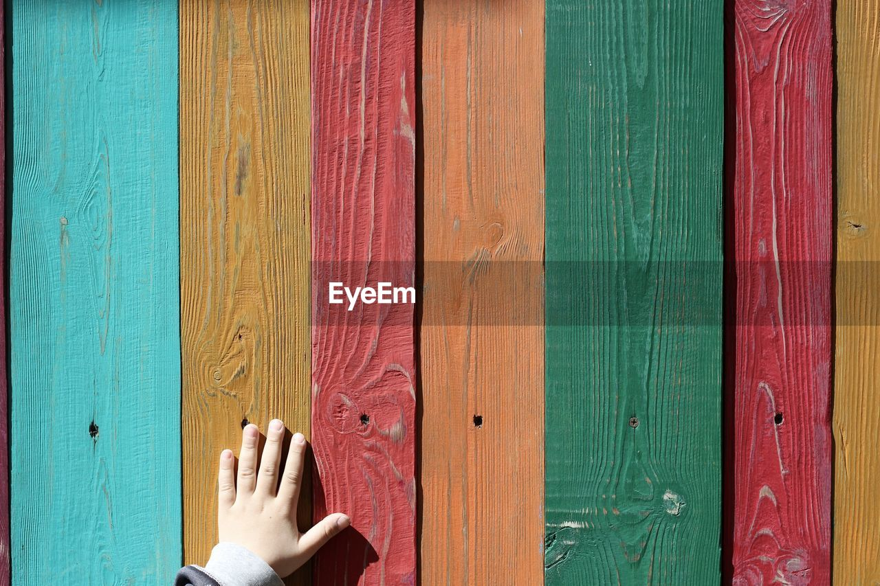 Cropped Hand Of Child Touching Colorful Painted Wooden Wall