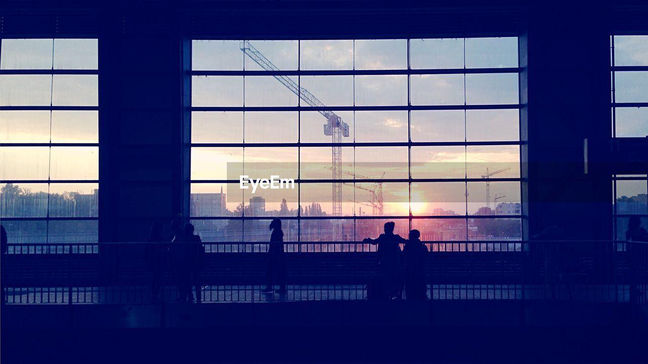 Silhouette people at s-bahnhof ostkreuz against sunset sky
