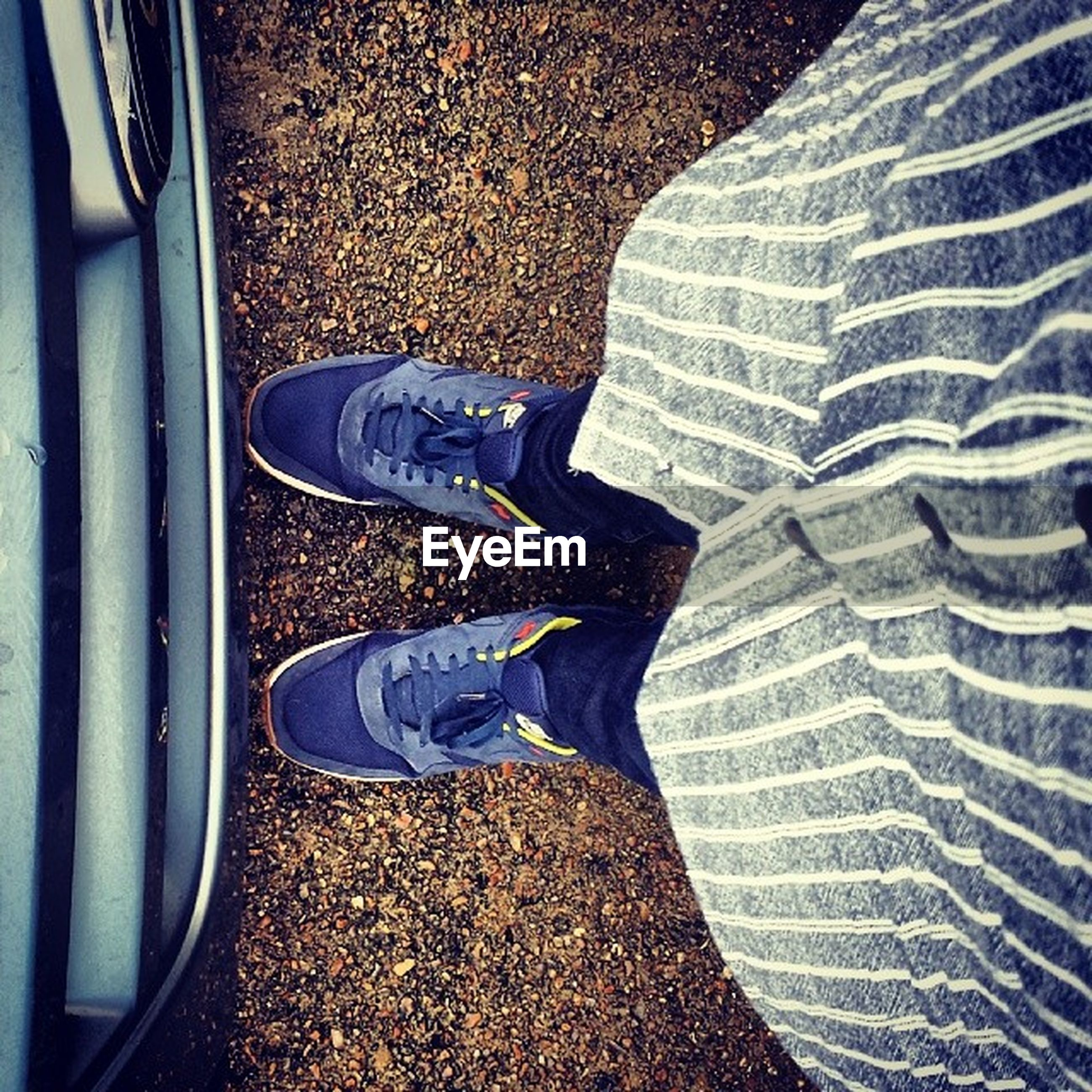 low section, shoe, person, footwear, personal perspective, high angle view, human foot, standing, jeans, lifestyles, directly above, canvas shoe, street, relaxation, part of, leisure activity, pair