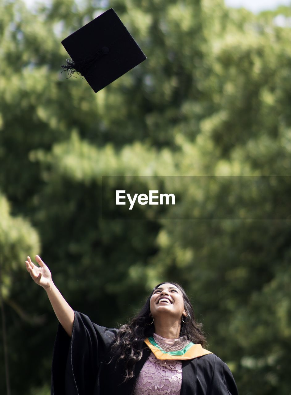 Woman throwing mortarboard in air against trees