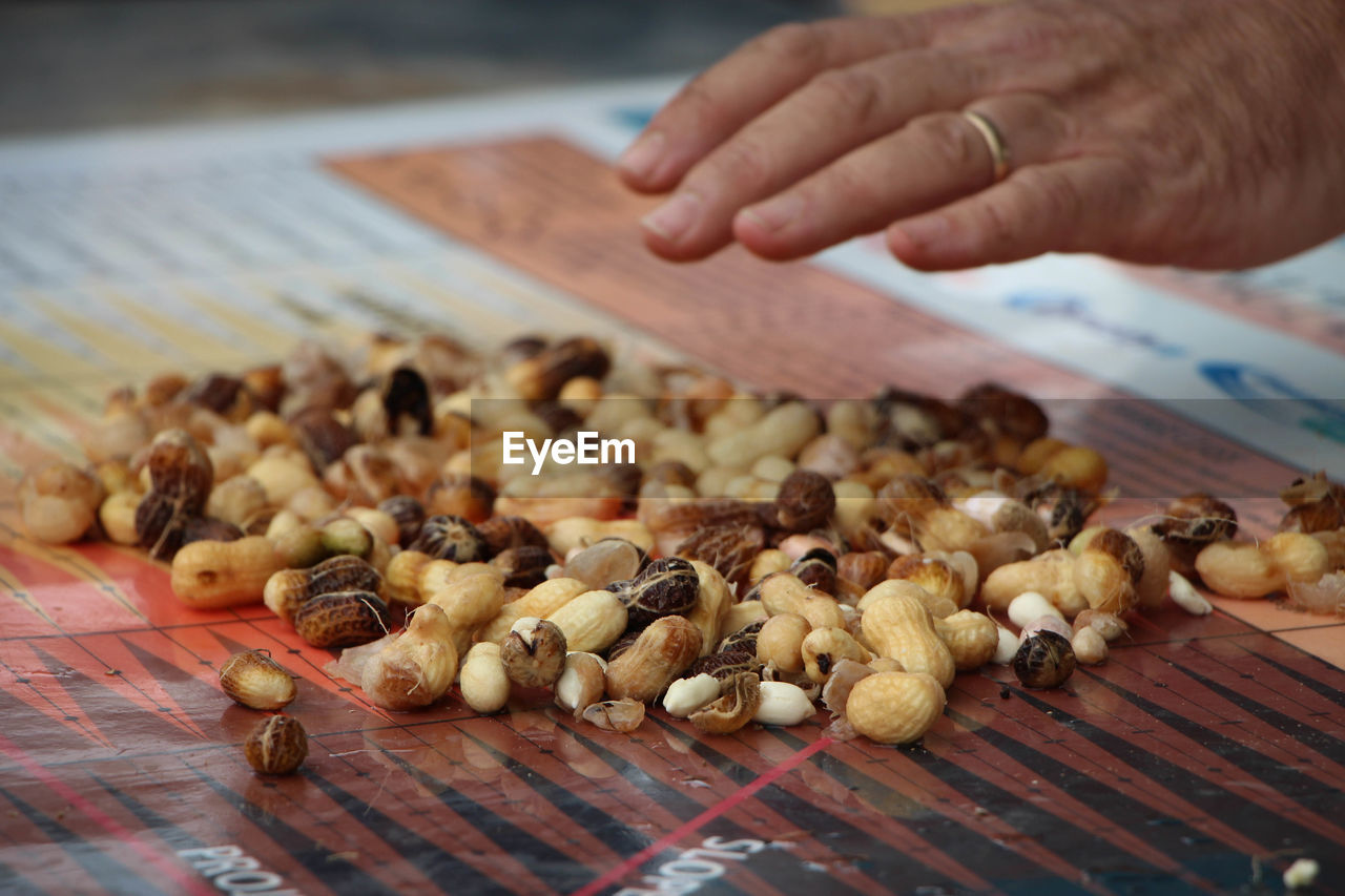 Cropped image of hand over peanuts on table