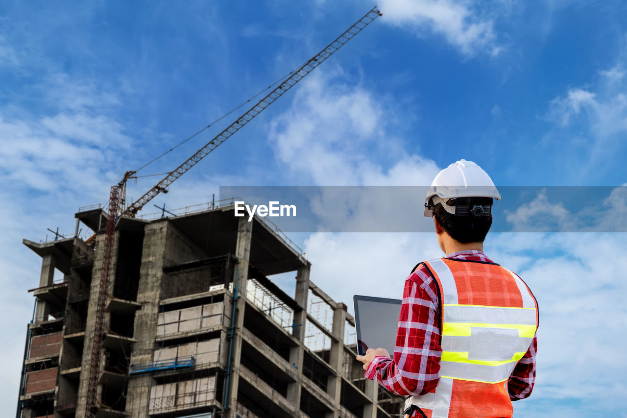 REAR VIEW OF MAN AT CONSTRUCTION SITE