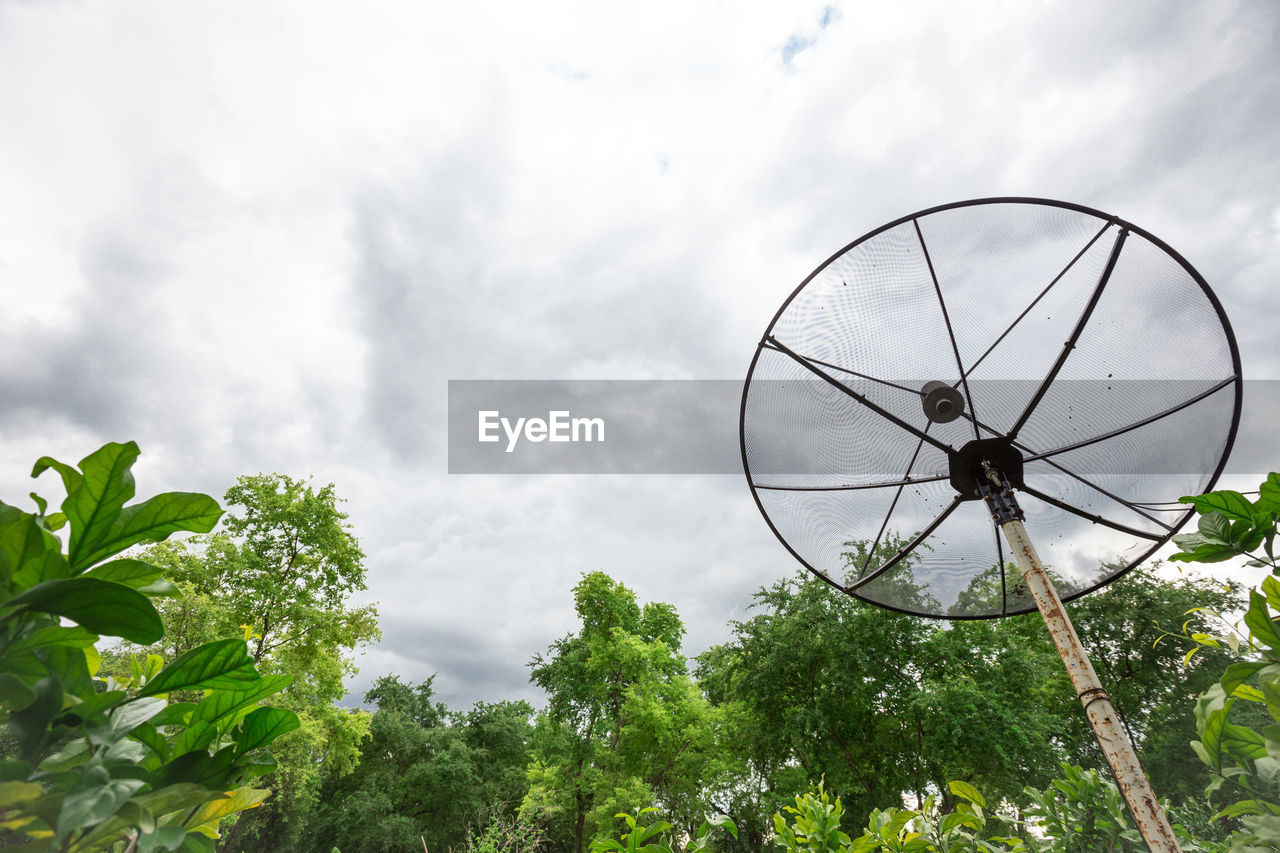 cloud - sky, sky, plant, tree, day, nature, low angle view, outdoors, satellite, no people, connection, satellite dish, technology, communication, green color, built structure, growth, shape, antenna - aerial, global communications