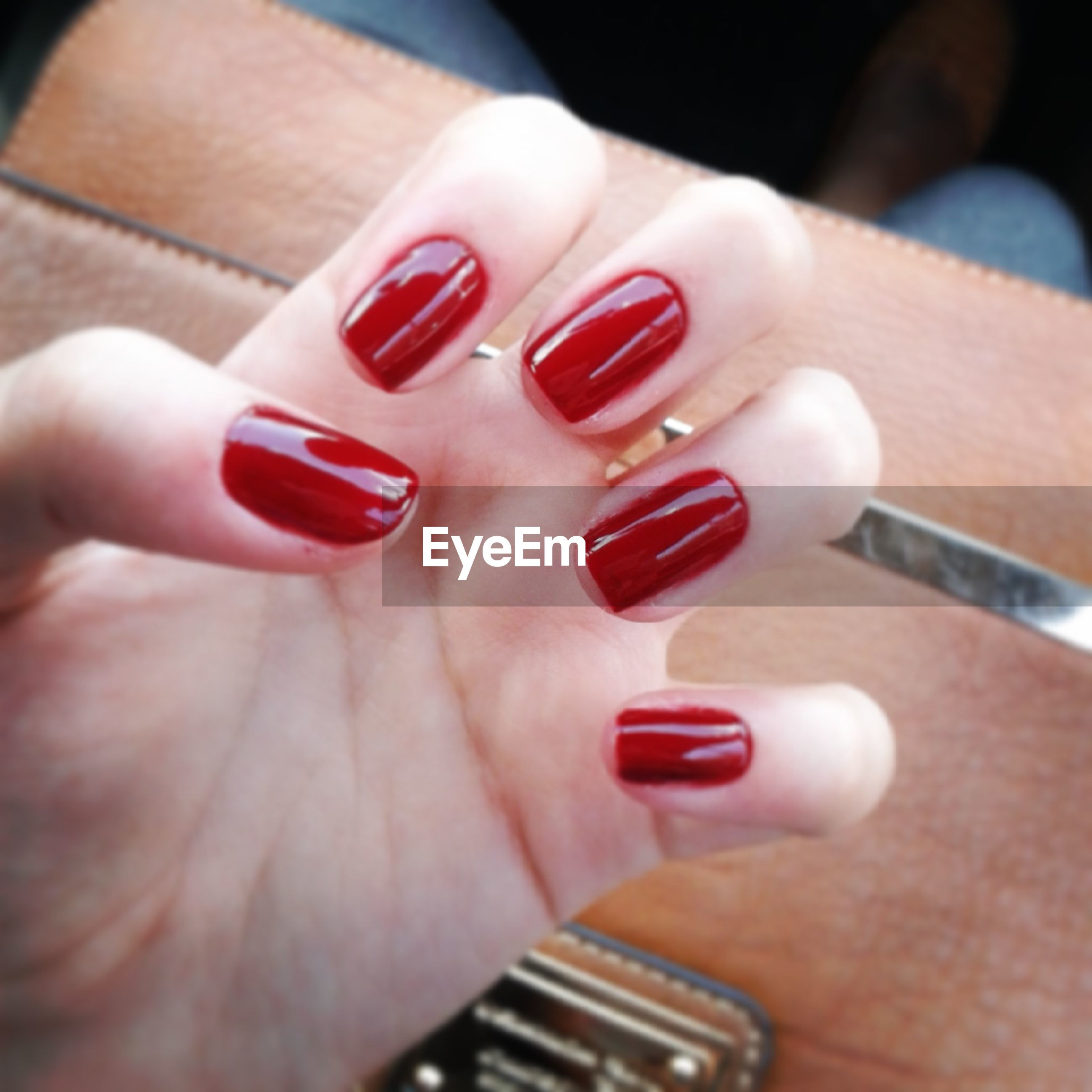 person, holding, indoors, part of, human finger, cropped, close-up, unrecognizable person, nail polish, focus on foreground, high angle view, showing, lifestyles, ring, red, table, selective focus