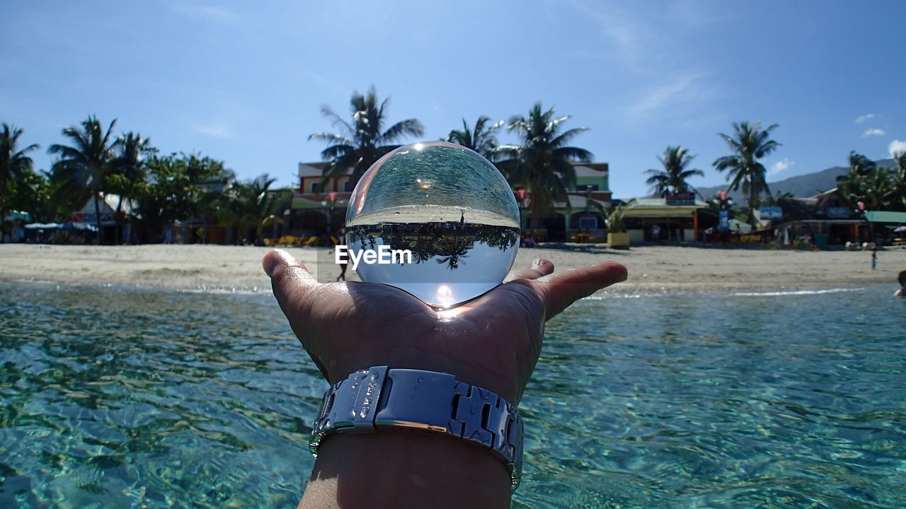 Cropped image of hand holding crystal ball at beach against sky