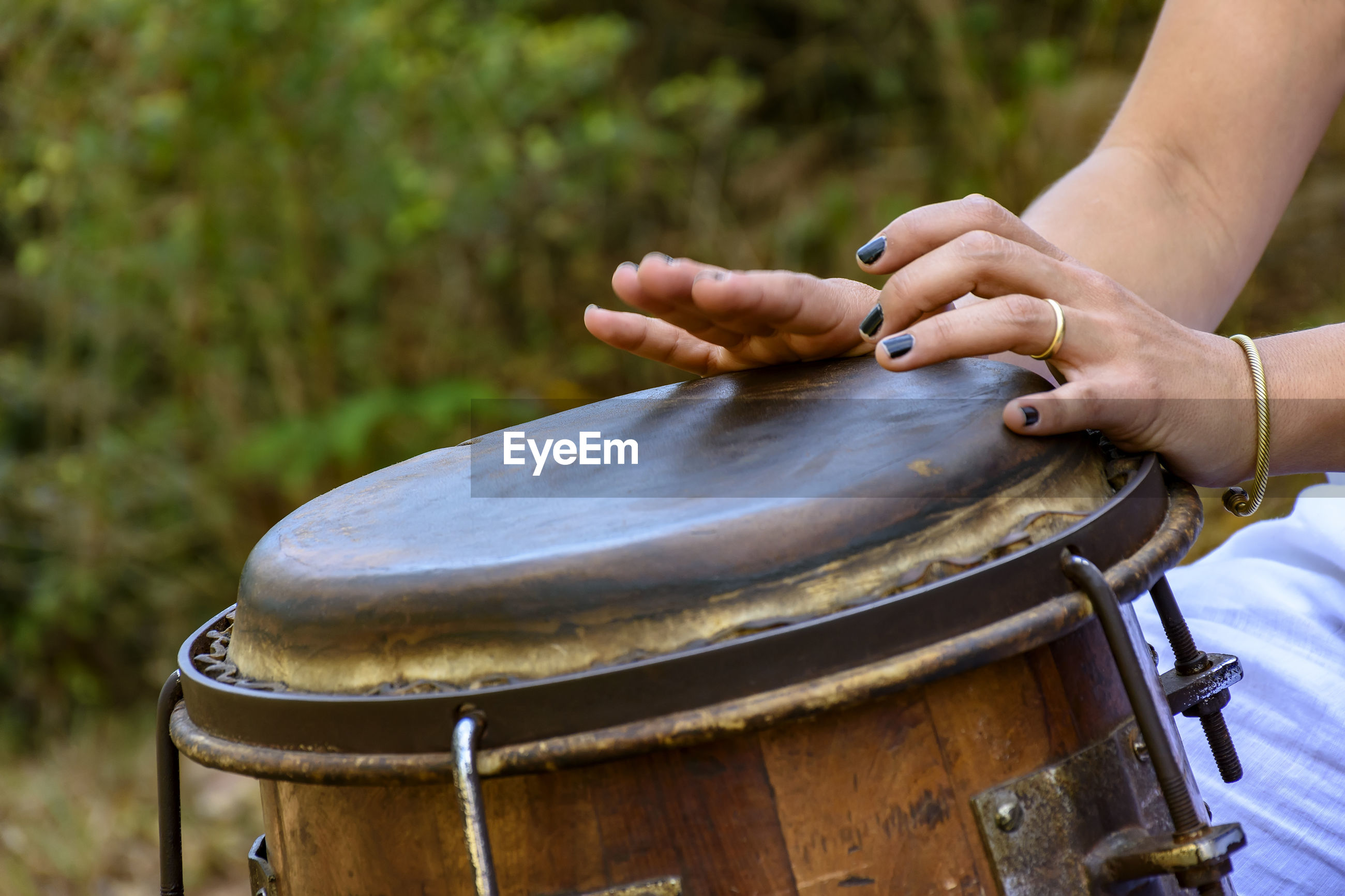 Cropped hands of woman playing drum outdoors