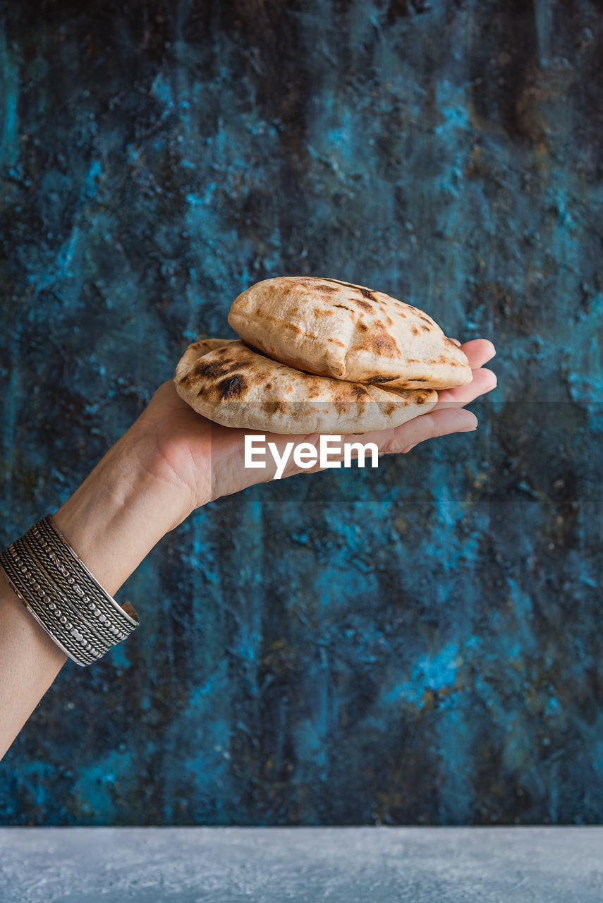 Cropped hand of woman holding flatbread against wall