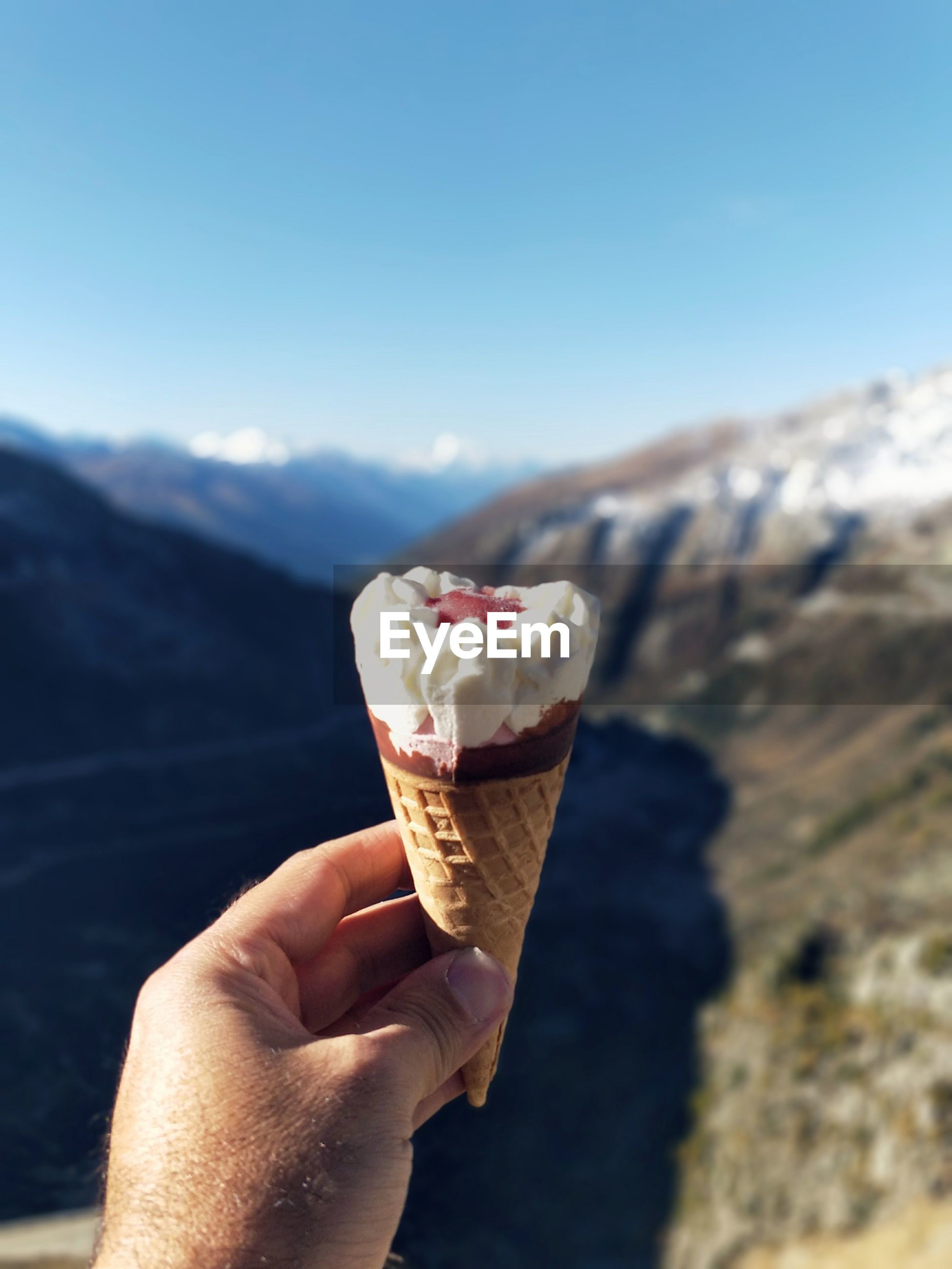 Cropped hand of man holding ice cream against mountain
