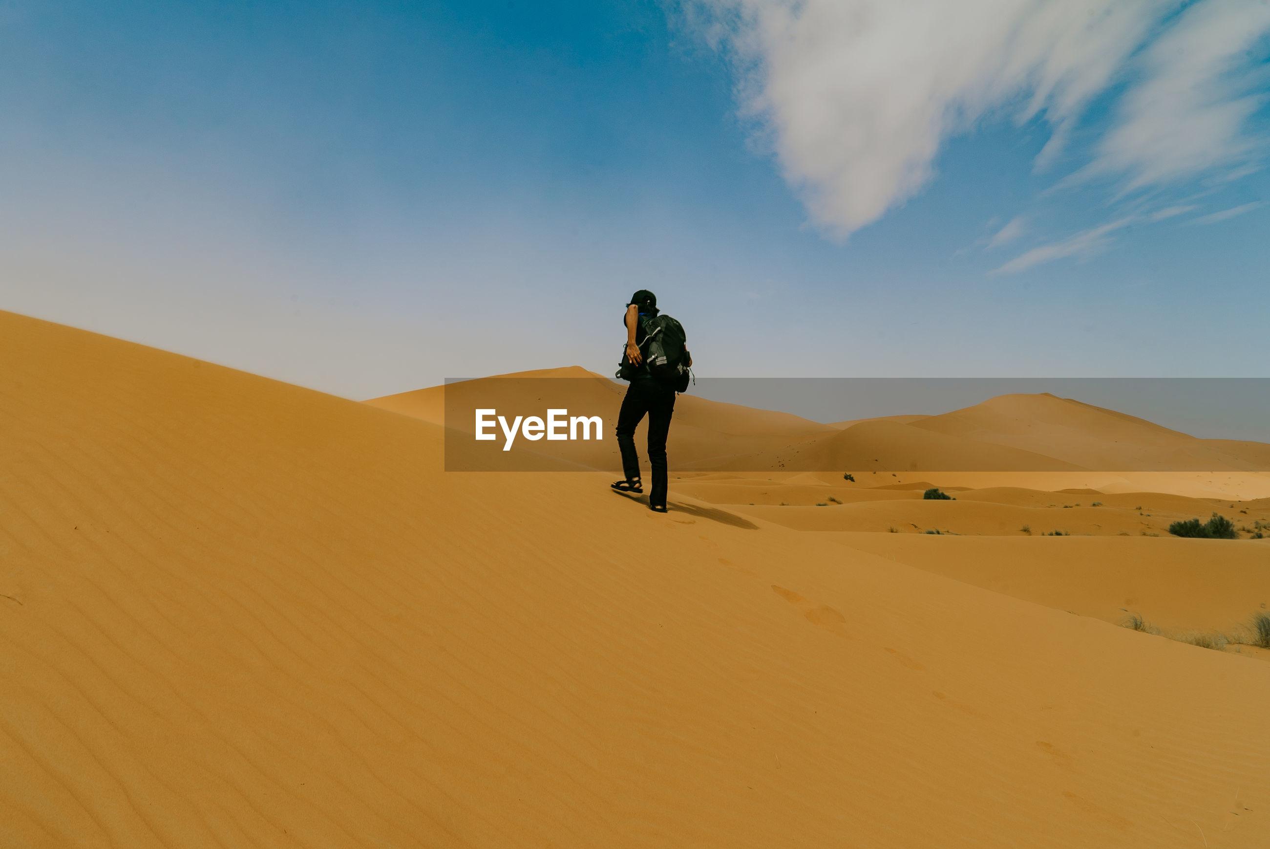 Full length man standing on sand dune in desert against sky