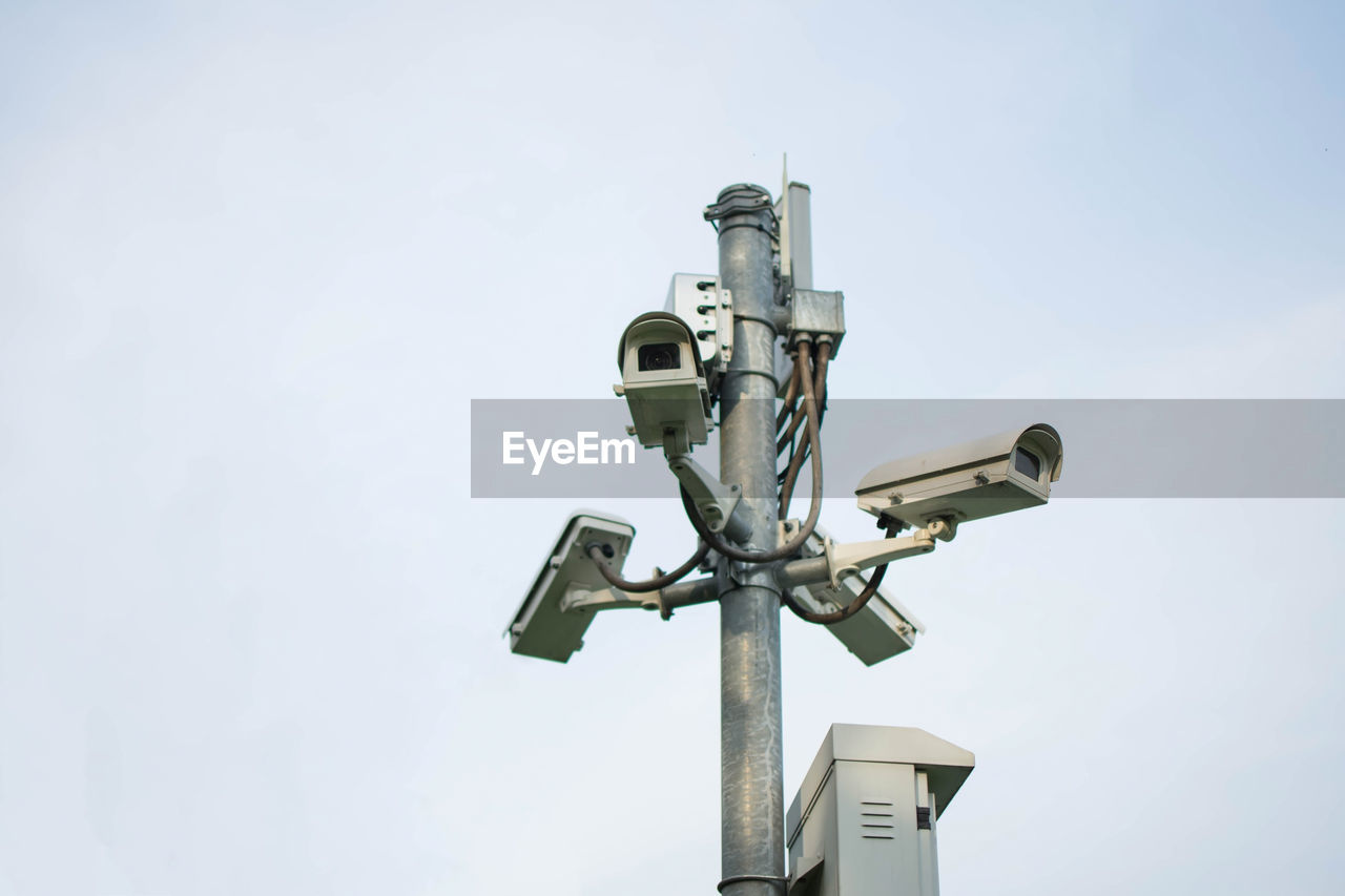 Low Angle View Of Security Cameras Against Clear Sky