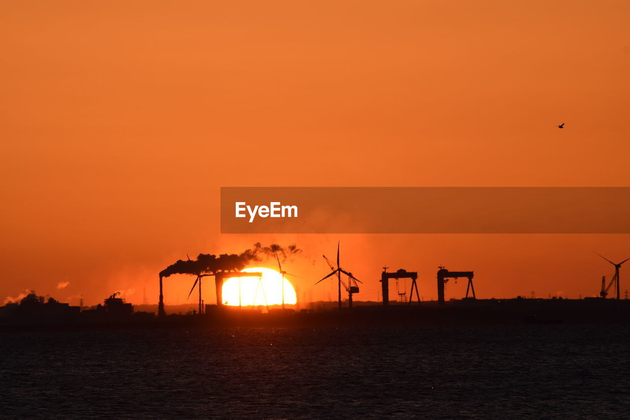 sunset, orange color, fuel and power generation, silhouette, sun, environmental conservation, alternative energy, industry, sky, renewable energy, wind power, wind turbine, nature, sea, windmill, scenics, outdoors, sustainable resources, beauty in nature, no people, built structure, factory, water, technology, industrial windmill, drilling rig