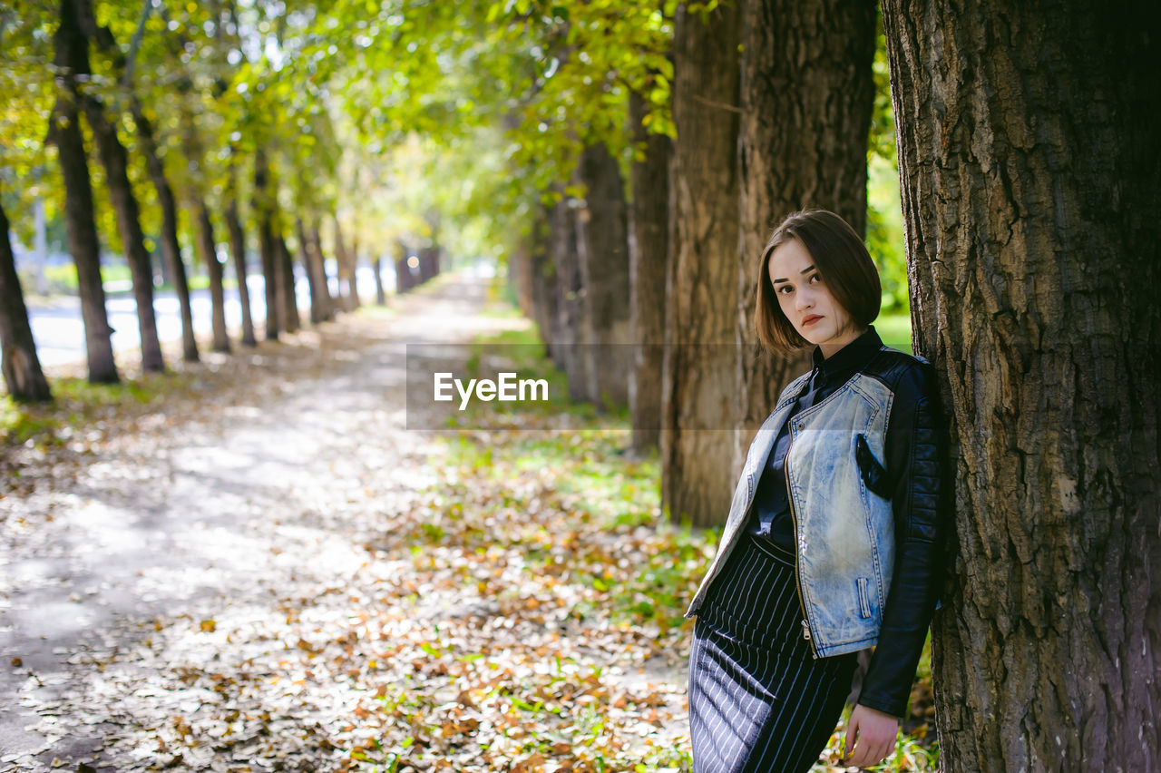 Portrait of young woman standing amidst trees at park