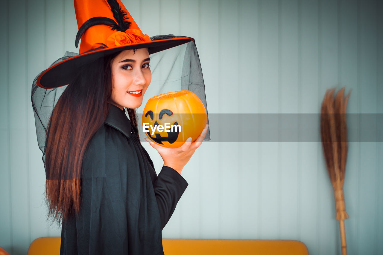 halloween, one person, food and drink, real people, orange color, food, pumpkin, women, hat, standing, smiling, holding, celebration, waist up, portrait, clothing, jack o' lantern, indoors, costume, witch