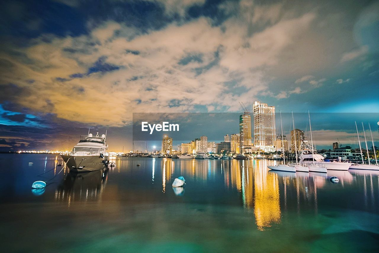 water, sky, cloud - sky, reflection, nautical vessel, building exterior, architecture, built structure, waterfront, transportation, nature, mode of transportation, city, sea, no people, sunset, illuminated, moored, harbor, outdoors, skyscraper, cityscape, office building exterior, marina, bay, yacht, wooden post