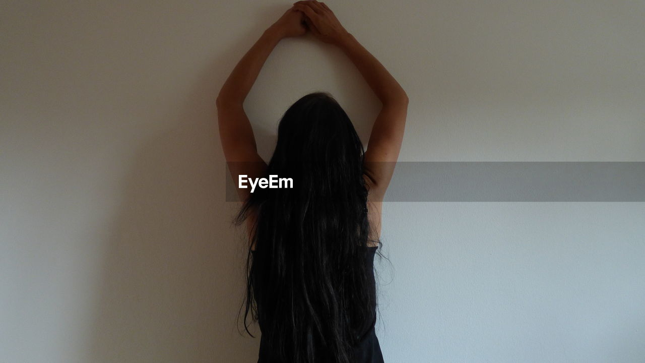 one person, hair, long hair, women, hairstyle, indoors, real people, lifestyles, wall - building feature, black hair, adult, waist up, rear view, leisure activity, arms raised, human arm, standing, human hair, young adult, obscured face