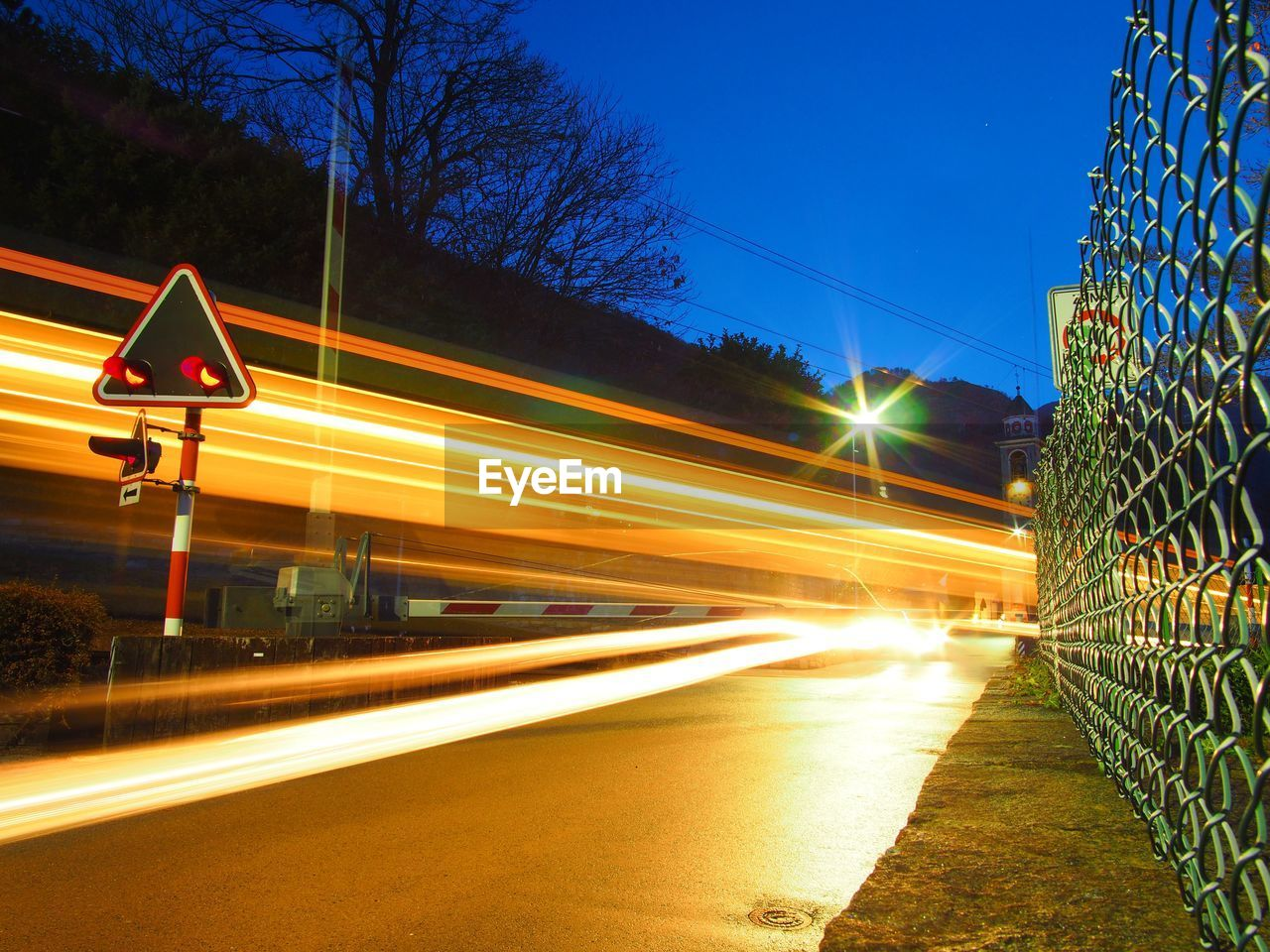 ILLUMINATED LIGHT TRAILS ON HIGHWAY AT NIGHT