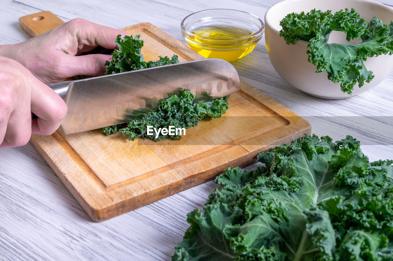 HIGH ANGLE VIEW OF MAN CUTTING BOARD