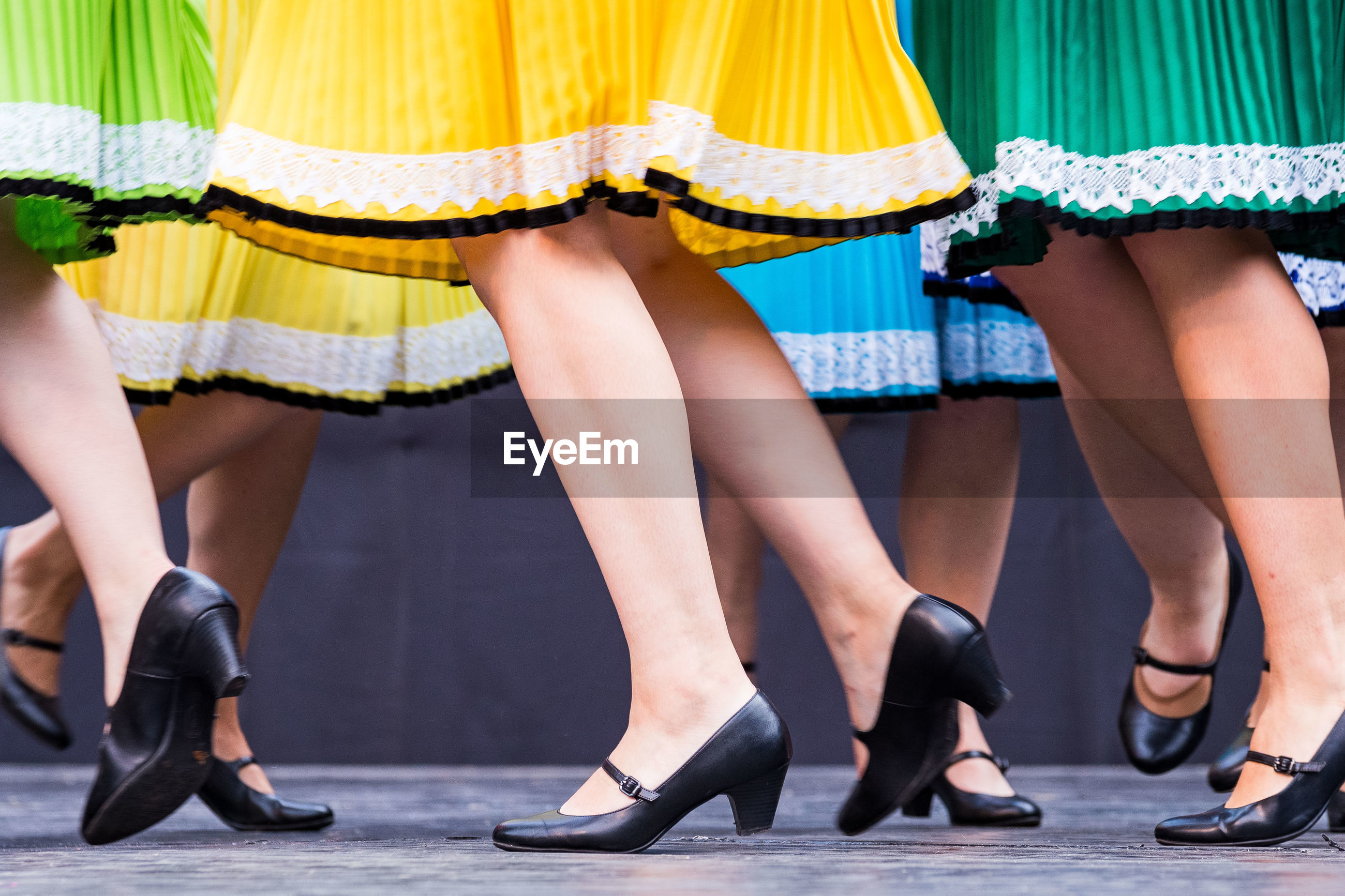 Low section of women in skirts walking on footpath