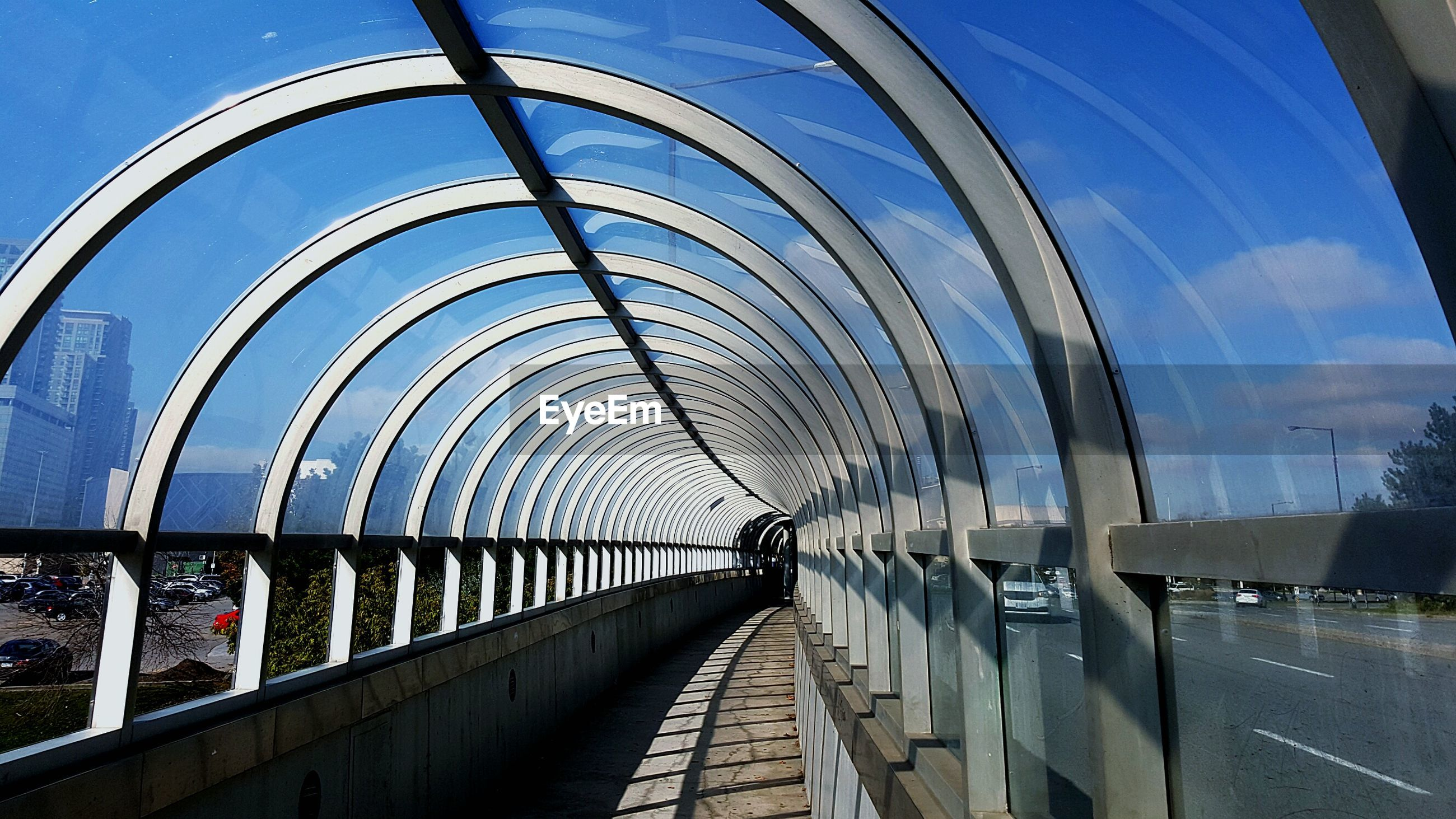 architecture, built structure, blue, the way forward, arch, transportation, diminishing perspective, indoors, vanishing point, railing, sky, building exterior, day, connection, bridge - man made structure, empty, sunlight, in a row, incidental people, no people