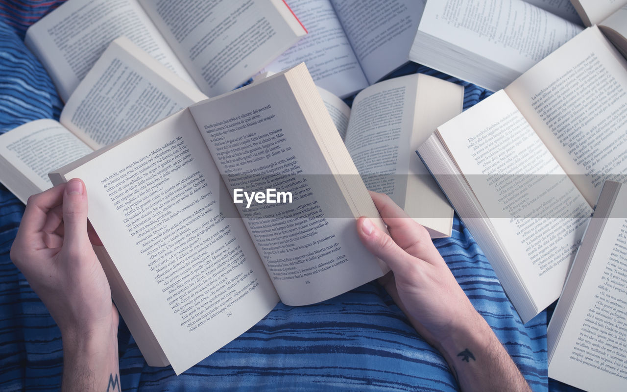 book, education, learning, page, human hand, real people, knowledge, studying, holding, high angle view, human body part, text, indoors, open, literature, lifestyles, paper, two people, student, university student, women, close-up, day