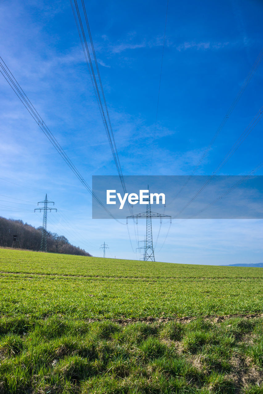 electricity, fuel and power generation, power line, sky, cable, power supply, electricity pylon, field, technology, landscape, land, connection, environment, nature, tranquil scene, tranquility, plant, grass, no people, scenics - nature, outdoors, complexity, electrical equipment, telephone line