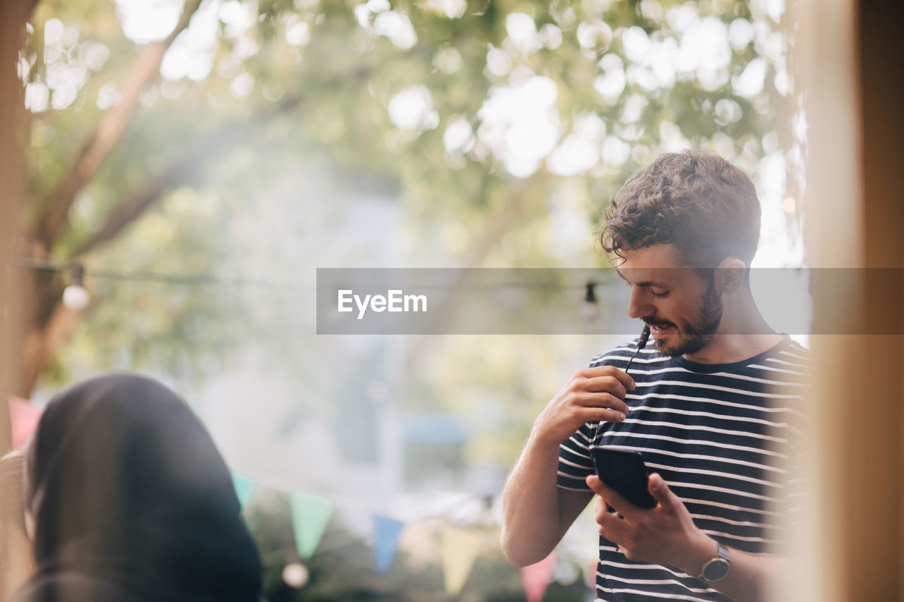 real people, lifestyles, one person, leisure activity, young adult, holding, selective focus, communication, technology, headshot, young men, wireless technology, mobile phone, standing, men, portrait, looking, day, outdoors