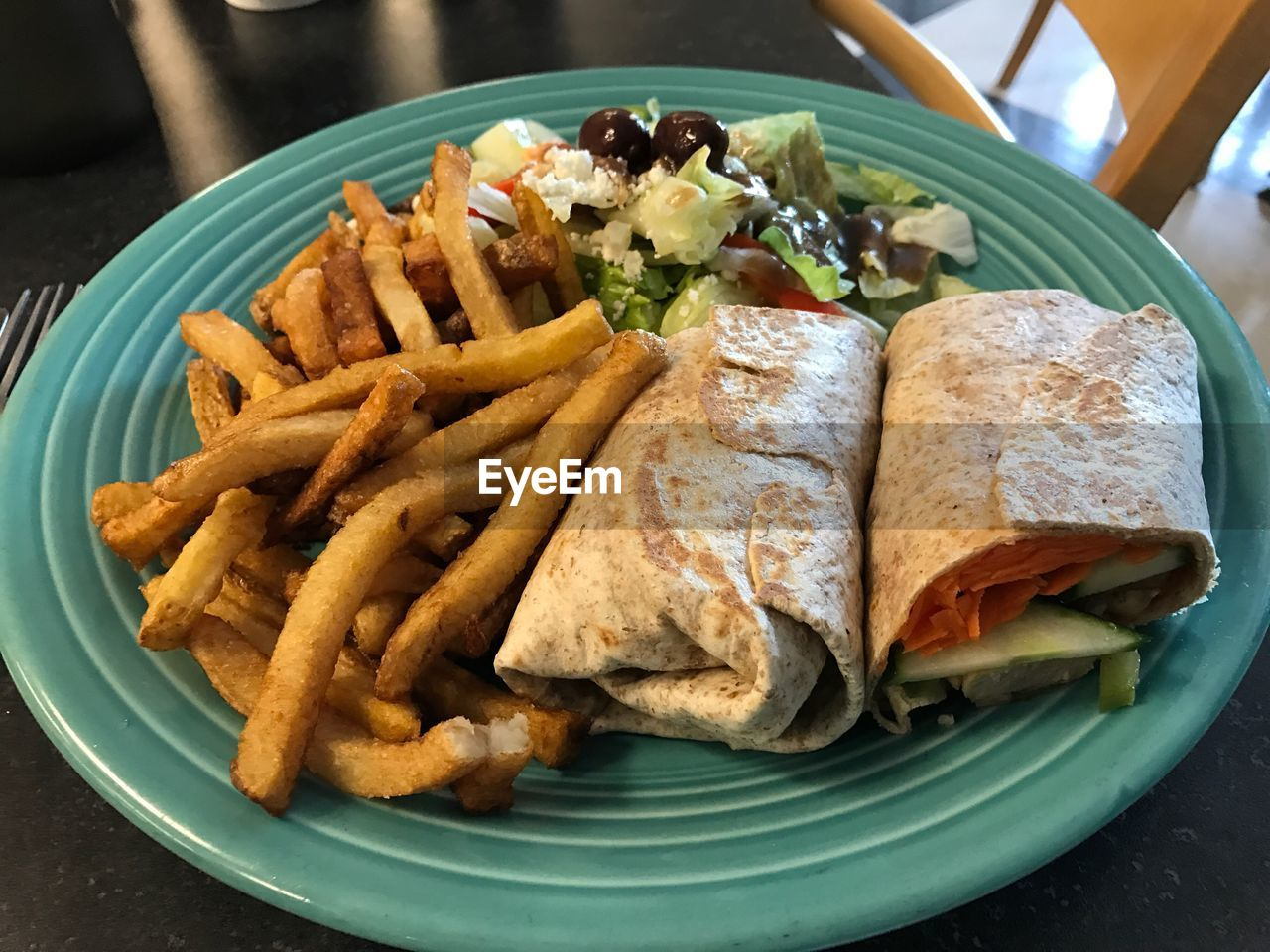 Close-up of spare rib wrap with french fries and greek salad served on table