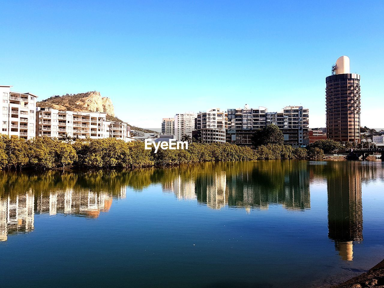 architecture, building exterior, built structure, reflection, clear sky, skyscraper, waterfront, tree, city, no people, water, outdoors, blue, growth, day, modern, cityscape, nature, sky