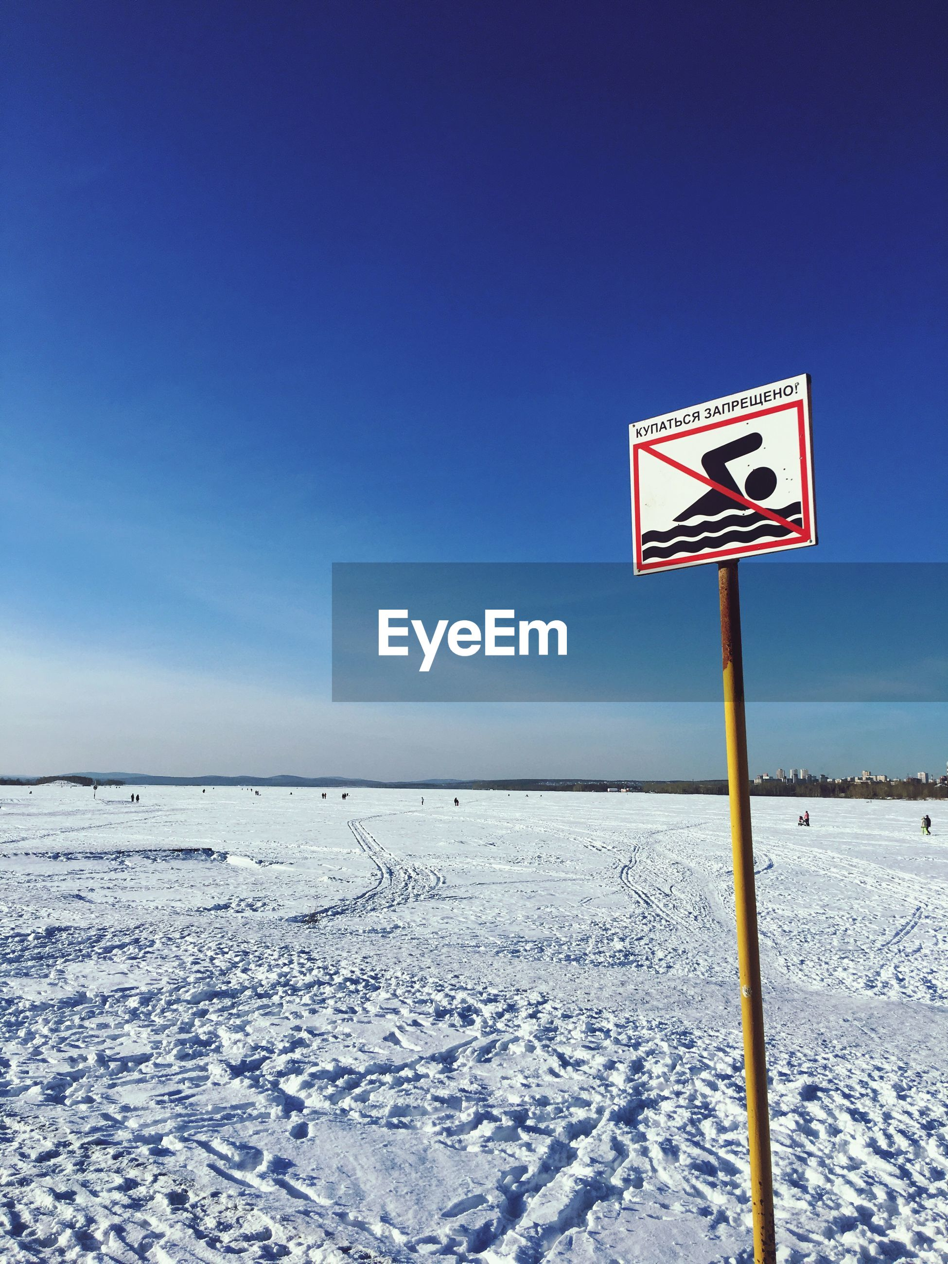 Warning sign on snow covered field against blue sky