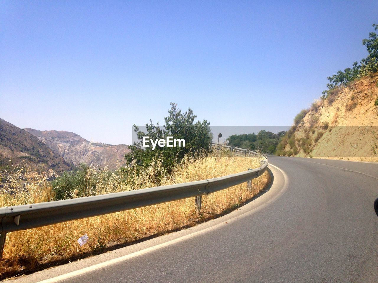road, sky, mountain, transportation, tree, the way forward, direction, plant, clear sky, nature, day, no people, tranquility, tranquil scene, beauty in nature, landscape, copy space, scenics - nature, environment, empty road, outdoors, crash barrier, long