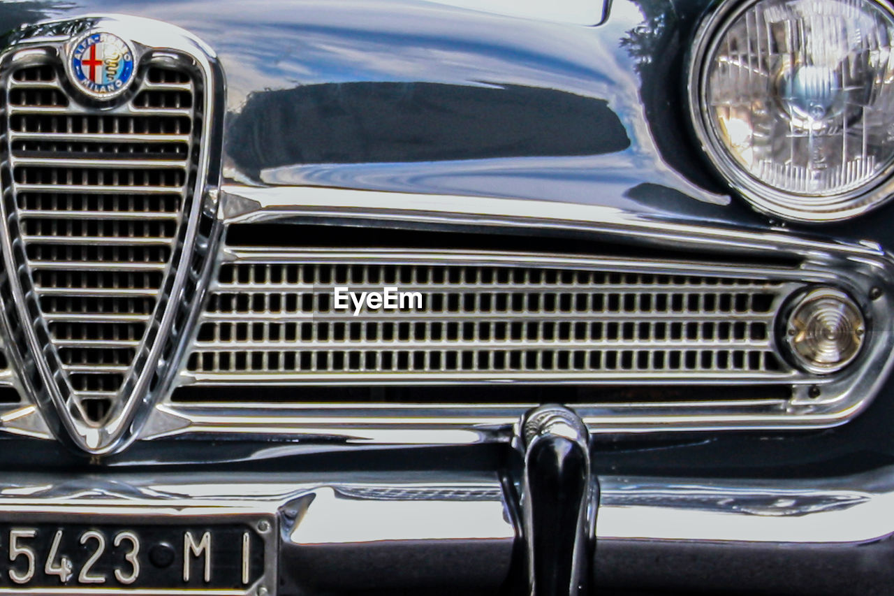 car, mode of transportation, motor vehicle, land vehicle, retro styled, transportation, headlight, close-up, metal, vintage car, no people, day, luxury, outdoors, wealth, shiny, grate, metal grate, grid, antique, chrome, silver colored, vehicle light