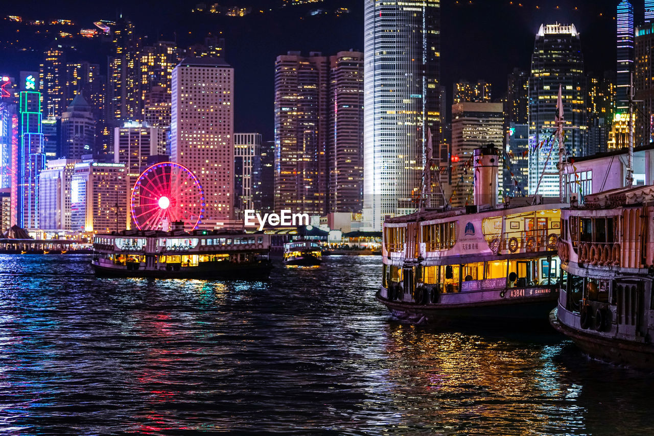 architecture, building exterior, built structure, city, illuminated, water, night, nautical vessel, waterfront, building, office building exterior, transportation, river, mode of transportation, modern, reflection, no people, skyscraper, landscape, outdoors, cityscape, passenger craft, financial district