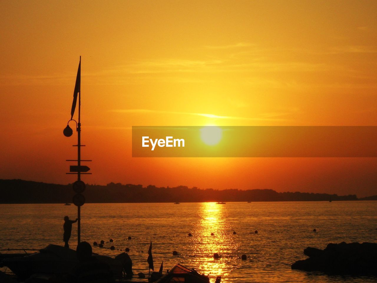 sunset, water, orange color, sun, beauty in nature, sea, scenics, nature, silhouette, sky, tranquility, sunlight, reflection, no people, outdoors, nautical vessel, scenery