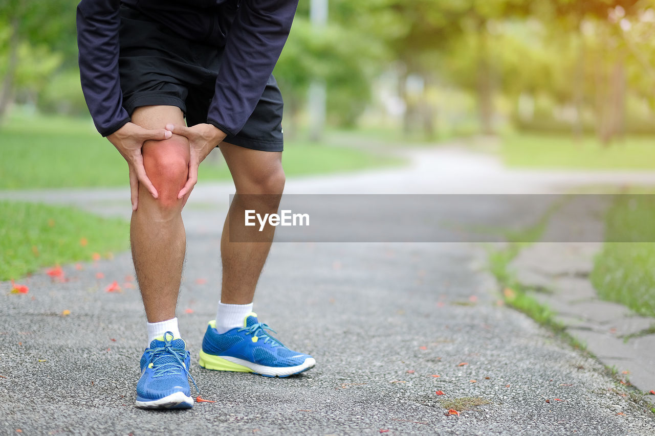Low Section Of Man Touching Aching Knee While Standing On Footpath