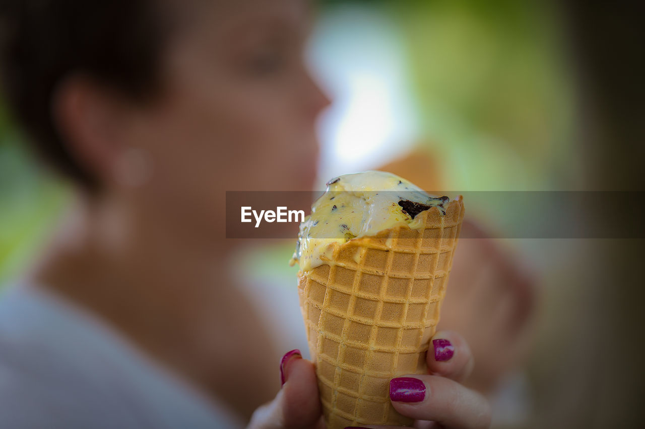 sweet food, food, ice cream, food and drink, ice cream cone, dairy product, one person, hand, cone, sweet, holding, focus on foreground, frozen food, indulgence, frozen, dessert, close-up, freshness, real people, lifestyles, temptation, outdoors, finger