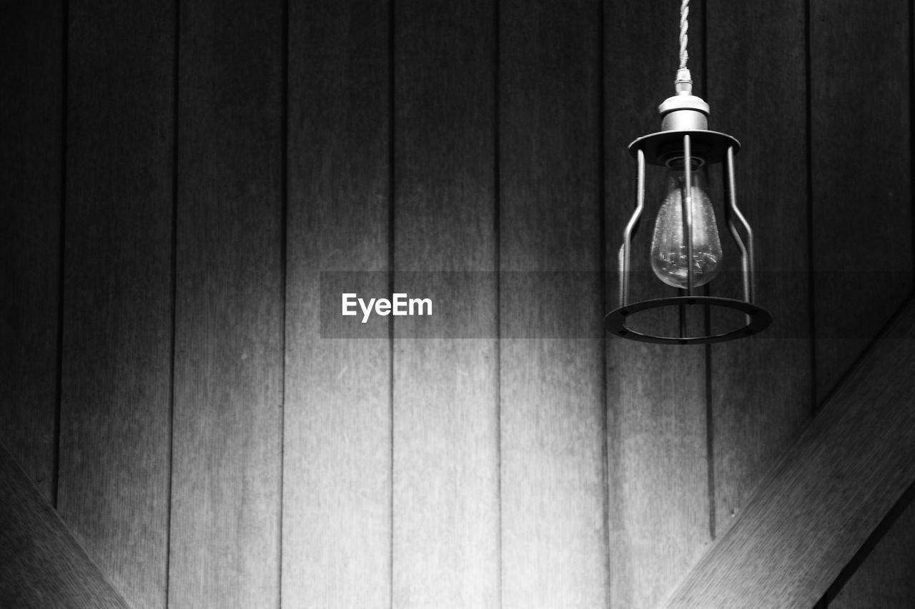 hanging, electricity, light bulb, no people, lighting equipment, indoors, wood - material, close-up, filament, technology, day